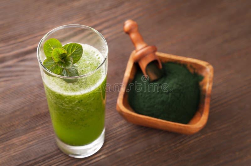 Batido verde com o spirulina no fundo de madeira foto de stock