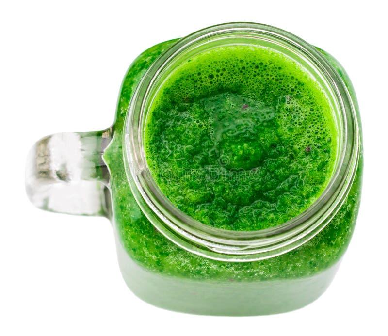 Batido verde saudável em uma caneca do frasco isolada na vista superior branca fotografia de stock