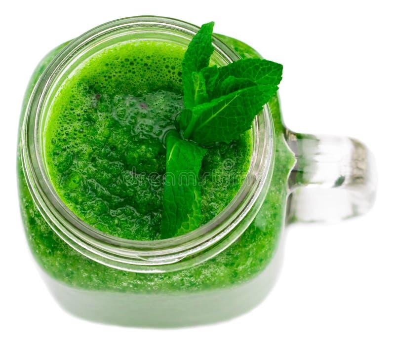 Batido verde saudável em uma caneca do frasco isolada na vista superior branca fotos de stock royalty free