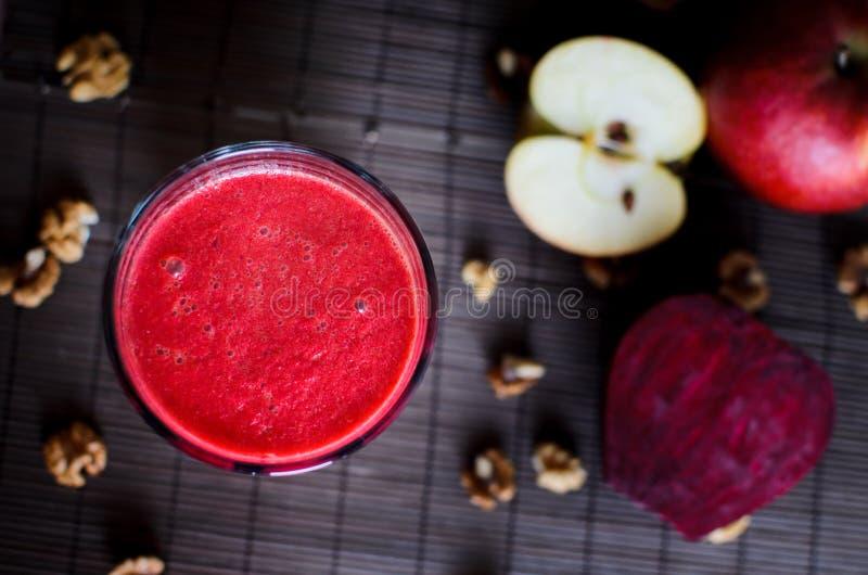 Batido vermelho do vegetariano cru fresco feito das beterrabas, da cenoura, da maçã e das nozes no fundo escuro, de madeira, vist imagens de stock royalty free