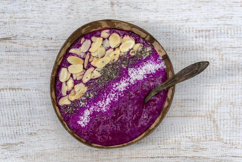 Batido vermelho na bacia do coco com fruto do dragão, abacate, flocos da amêndoa, microplaquetas do coco e sementes do chia para  fotografia de stock