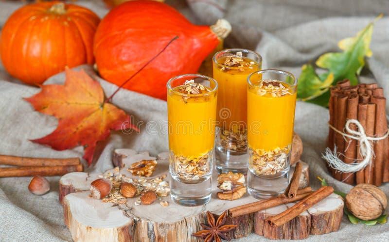 Batidos da abóbora com porcas, canela, gengibre e granola Nutrição útil Sobremesas do outono imagem de stock