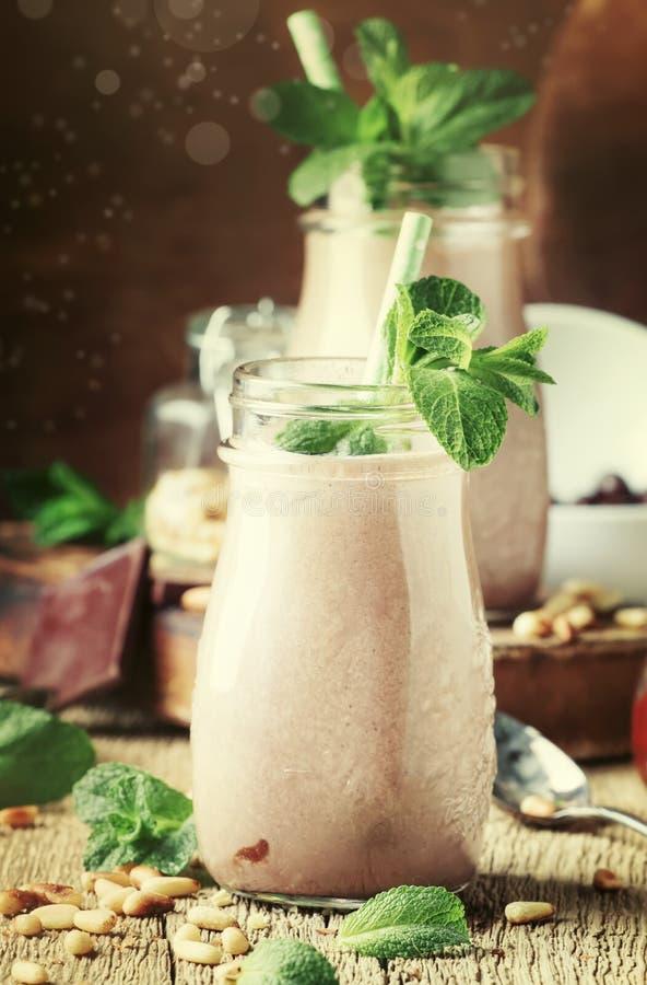 Batidos da hortelã do chocolate ou cocktail do leite com as porcas de cedro nas garrafas de vidro no fundo de madeira velho da me imagem de stock