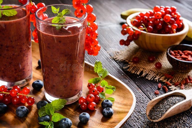 Batidos de fruta com corintos vermelhos, mirtilo, banana, bagas do goji e sementes do chia fotografia de stock