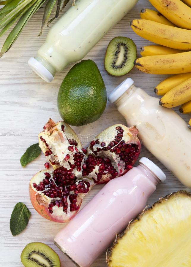 Batidos de fruta ou milk shake de v?rias cores nos frascos de vidro com frutos coloridos no fundo de madeira branco, vista superi fotografia de stock