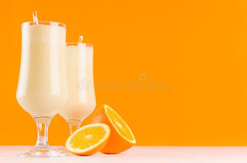 Batidos de leche brillantes de las naranjas con la fruta cítrica de las rebanadas, la paja rayada en la tabla de madera blanca y  foto de archivo