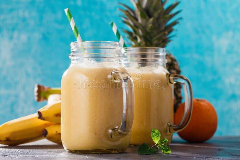 Batidos do abacaxi, da banana e da laranja em um frasco de vidro imagem de stock royalty free