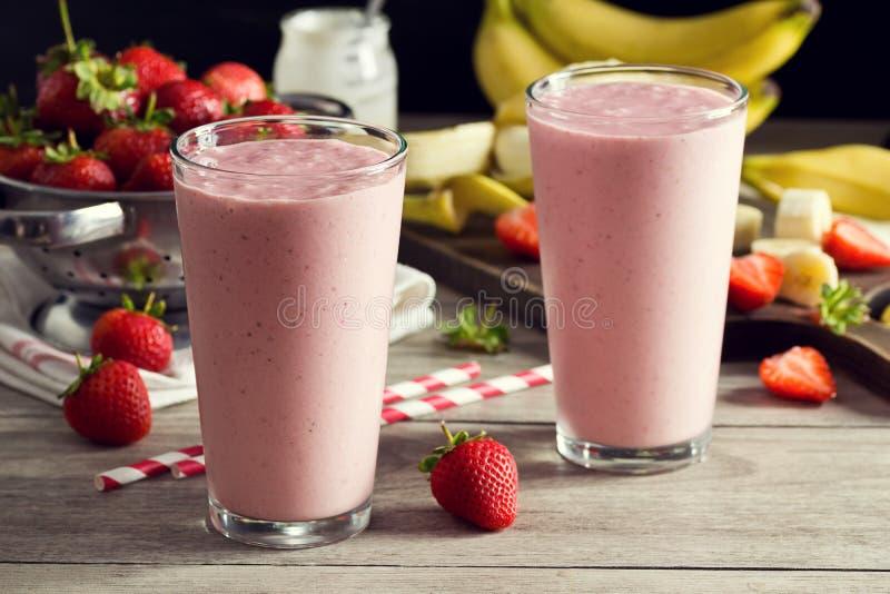 Batidos do iogurte da banana da morango com ingredientes foto de stock royalty free