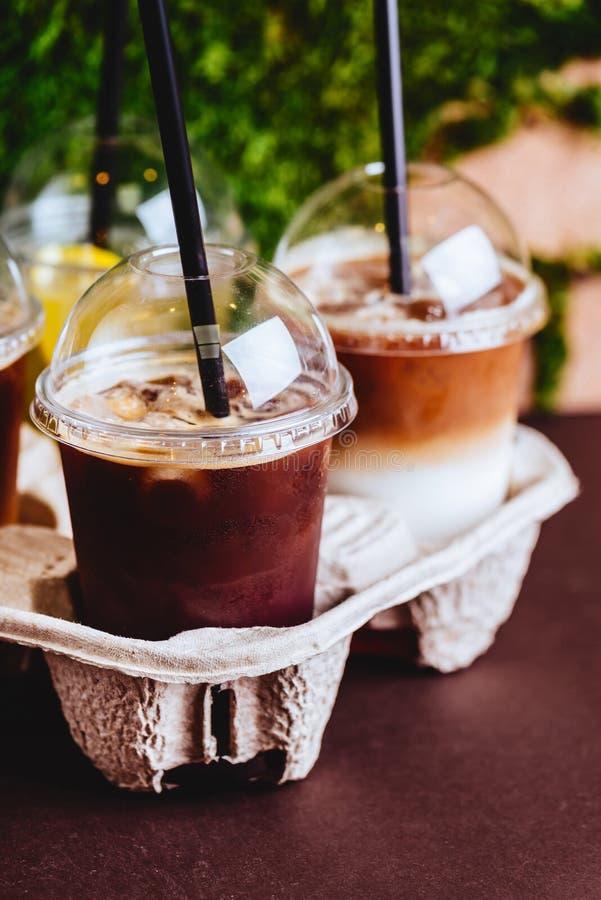 Batidos e café congelado no copo plástico no fundo de madeira da bandeja e da parede de tijolo no café imagem de stock royalty free