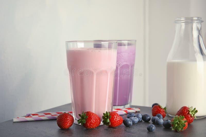 Batidos e ingredientes de leche deliciosos en la tabla foto de archivo
