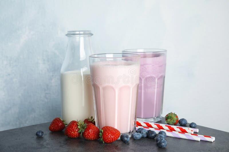 Batidos e ingredientes de leche deliciosos en la tabla fotos de archivo