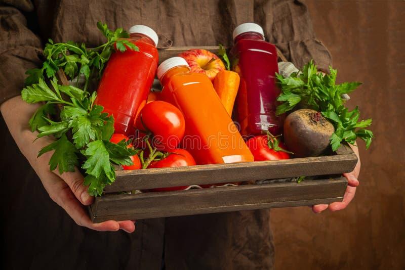 Batidos frescos do suco dos v?rios tomates da beterraba da ma?? da cenoura dos vegetais em umas garrafas em uma caixa de madeira  foto de stock