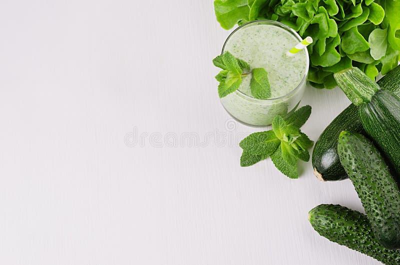 Batidos verdes saudáveis com hortelã da folha, verdes dos espinafres, palha, vegetais verdes na placa de madeira macia branca, es imagem de stock