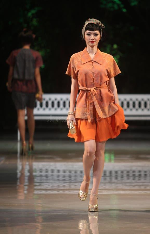 Batik de port de modèle femelle asiatique à la piste de défilé de mode photo stock