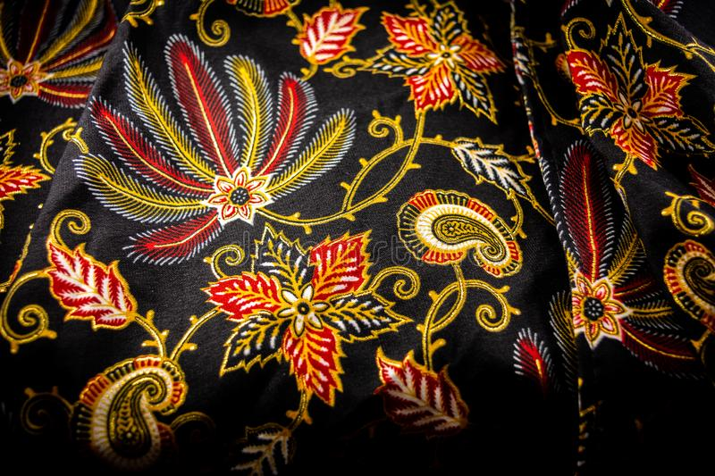 batik fabric with floral pattern and black basic color. textile and fashion industries, made in Indonesia royalty free stock image