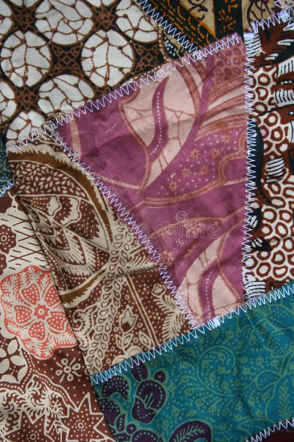 Batik material background, Indonesian material pieced together with white zigzag stiches in crazy quilt design in colorful blue gr stock photography