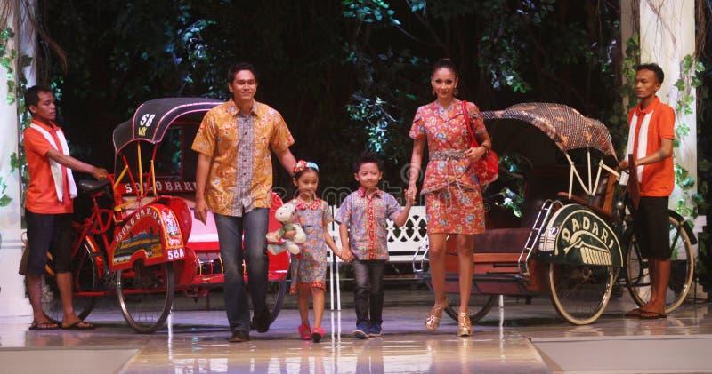 Batik que lleva modelo de la familia asiática en el desfile de moda r fotos de archivo