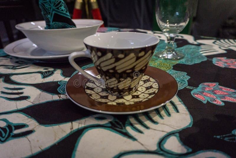 Batikmodelltryck på den keramiska koppen överst av tabellfotoet som tas i Batikmuseet Pekalongan Indonesien royaltyfri foto