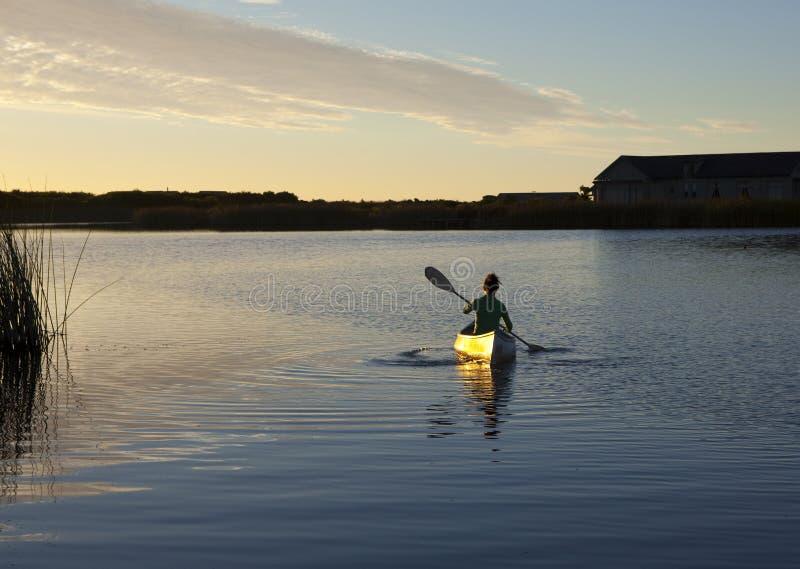 Batimiento de la canoa en la puesta del sol imagenes de archivo