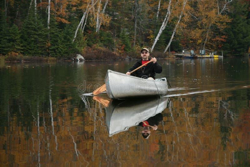 Batimiento de una canoa en un lago autumn imagen de archivo