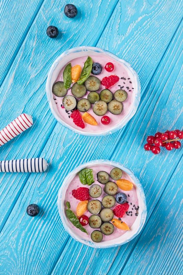 Batożący kwarka mousse z malinkami, czarnymi jagodami, czerwonym rodzynkiem i fizalis na błękitnym tle, Odgórny widok, bezpłatna  zdjęcie royalty free