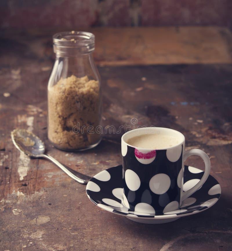 Batom no copo de café no ajuste rústico do café ou do estúdio foto de stock royalty free