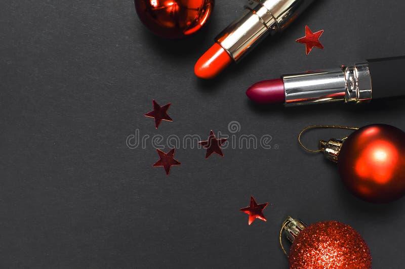 Batom vermelho, bolas do Natal, confetes no espaço colocado liso preto da cópia da opinião superior do fundo Composição e beleza  imagem de stock royalty free