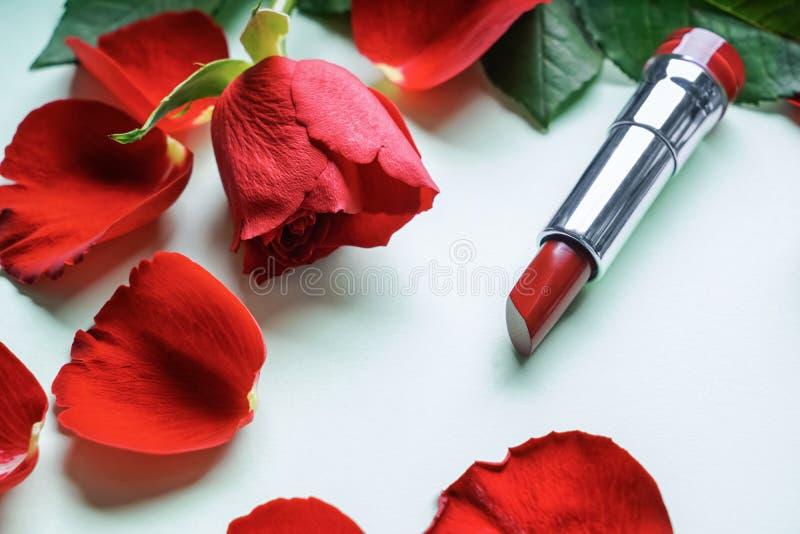 Batom vermelho com as pétalas cor-de-rosa no fundo branco fotos de stock royalty free
