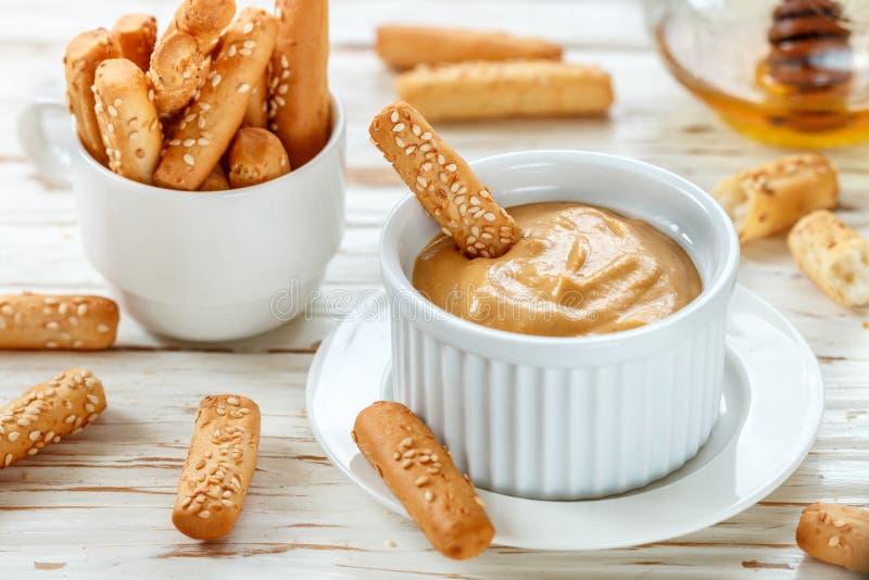 Batons de pain avec les graines de sésame avec de la sauce à immersion de moutarde et de miel image libre de droits