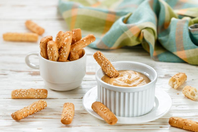 Batons de pain avec les graines de sésame avec de la sauce douce à immersion de moutarde Casse-croûte gastronome pour des gourmet photo stock