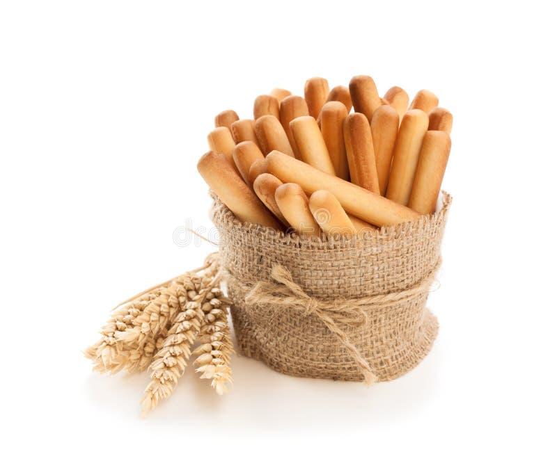 Batons de pain salés avec des oreilles de blé d'isolement sur le blanc photographie stock