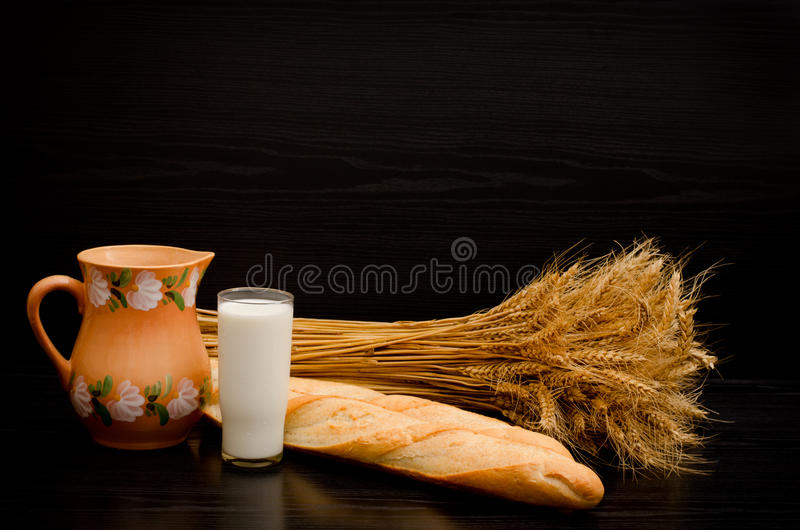Batons, a pitcher, a glass of milk and a sheaf on a black background stock photos