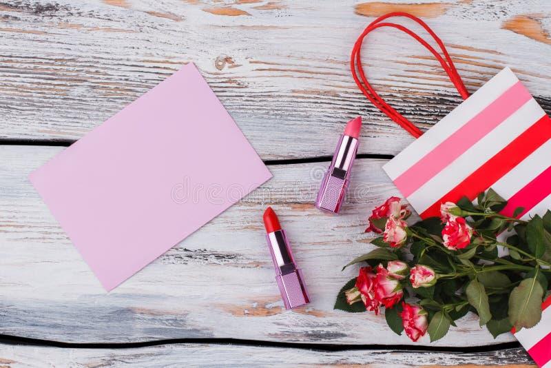 Batons, saco de compras, flores e papel vazio com rosas fotografia de stock royalty free