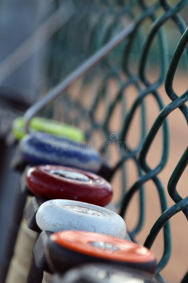 Baseball bat softball bats hanging on a fence. Old used bats hanging on a fence waiting to be used by little leaguers royalty free stock photos