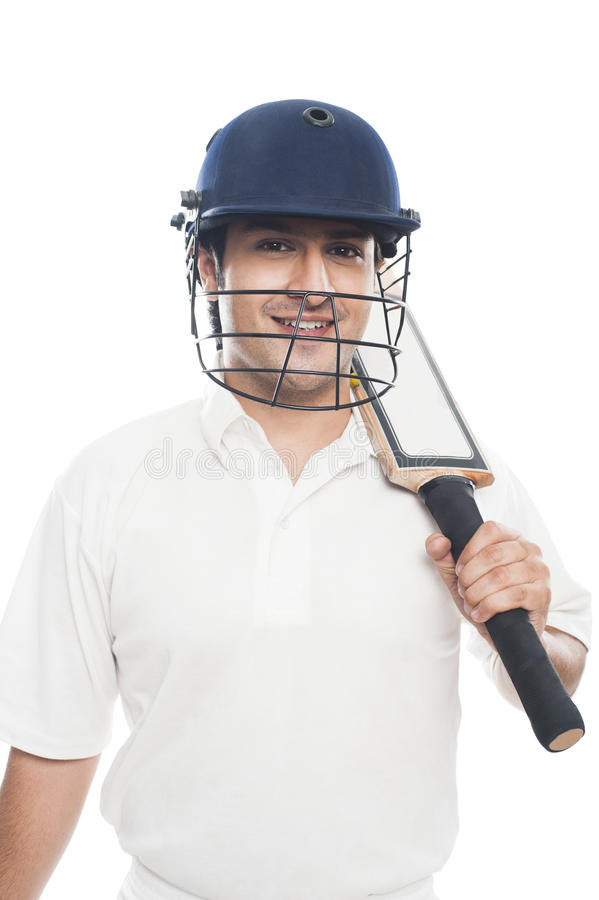Batsman with holding a cricket bat and smiling. Portrait of a batsman with holding a cricket bat and smiling stock image