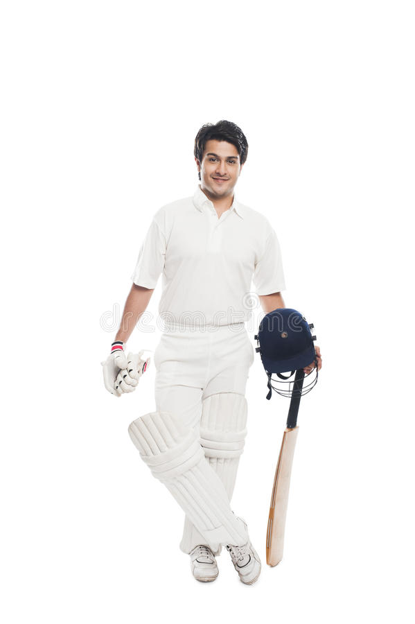 Batsman holding a cricket bat with sports helmet and smiling. Portrait of a batsman holding a cricket bat with sports helmet and smiling royalty free stock photo