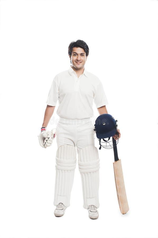 Batsman holding a cricket bat with sports helmet and smiling. Portrait of a batsman holding a cricket bat with sports helmet and smiling stock photo