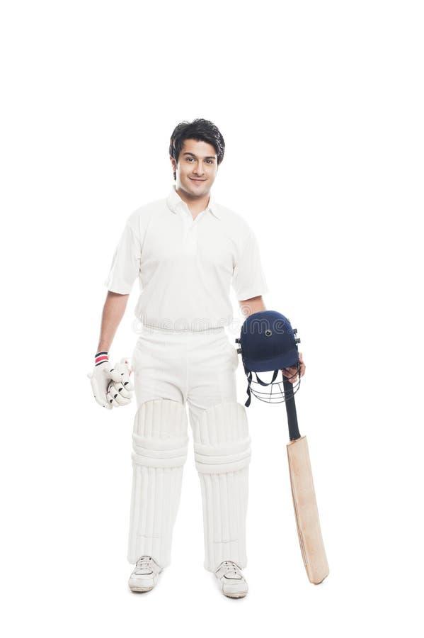 Batsman holding a cricket bat with sports helmet and smiling. Portrait of a batsman holding a cricket bat with sports helmet and smiling stock photography
