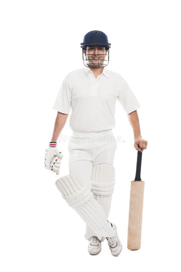 Batsman standing with a cricket bat. Portrait of a batsman standing with a cricket bat royalty free stock images
