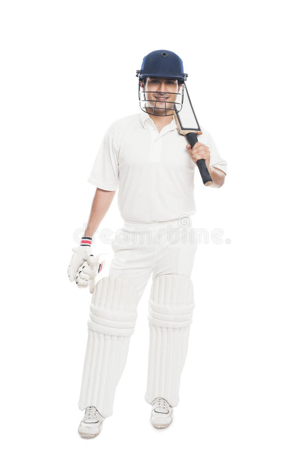 Batsman standing with holding a cricket bat and sm. Portrait of a batsman standing with holding a cricket bat and smiling stock photography
