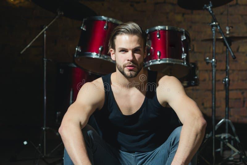 Batta dei tamburi Rock star o attuatore Godere della musica strumentale L'uomo bello si siede in scena allo strumento di percussi fotografia stock