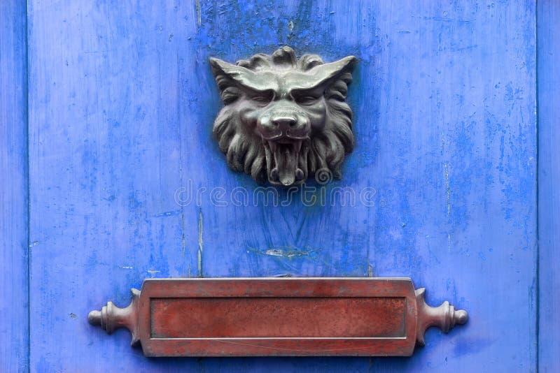Battacchio e cassetta della posta su una porta di legno blu fotografia stock