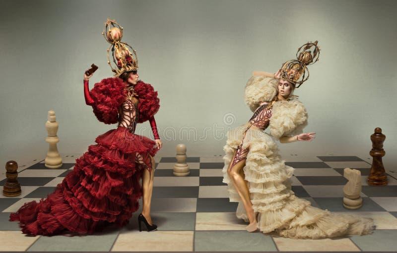 Battaglia delle regine di scacchi sulla scacchiera immagini stock