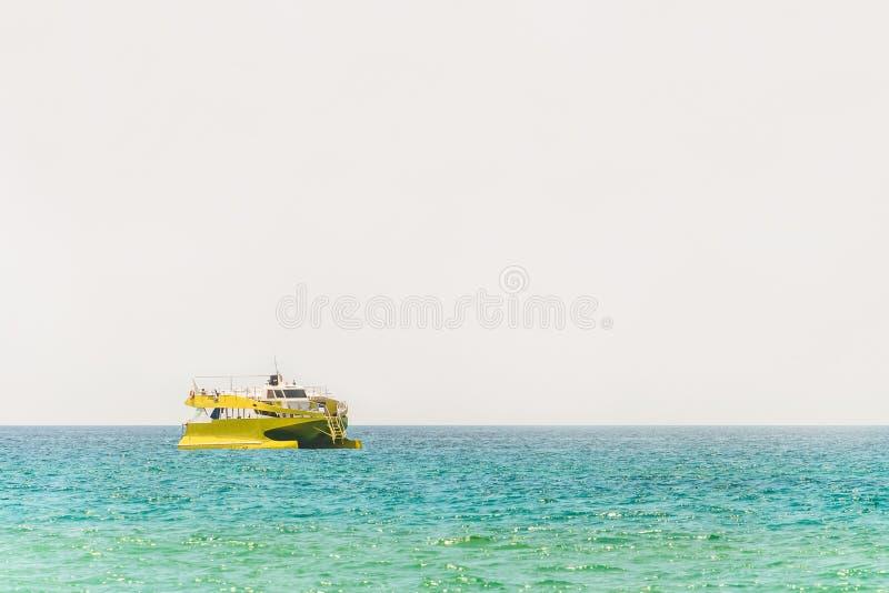 Battello da diporto giallo alle acque del turchese fotografie stock