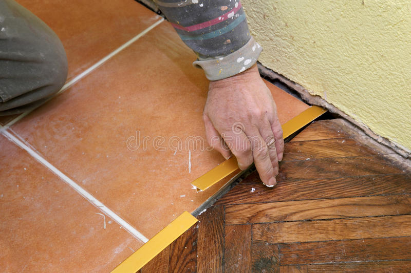 Batten placing. Home renovation, worker installing tile trim profiles royalty free stock images