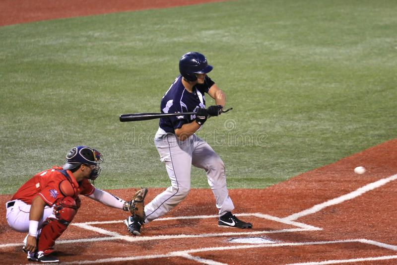 Batter swings the bat. Baseball hitter releases his swinging bat as the ball heads to the plate at the professional baseball game, Baseball Stadium, Lorain stock images