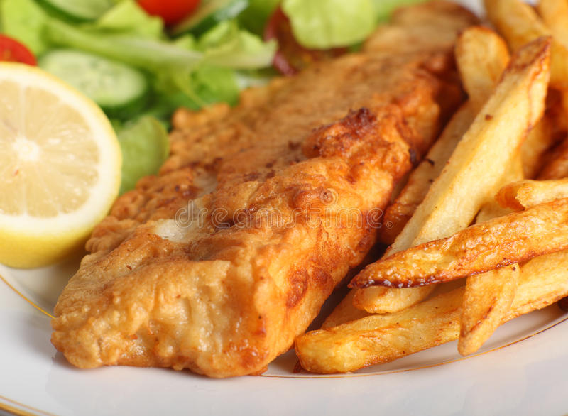 Battered fish with chips and salad. A piece of fish in batter served with french fried potato chips, lemon and a lettuce, rocket, cucumber and tomato salad