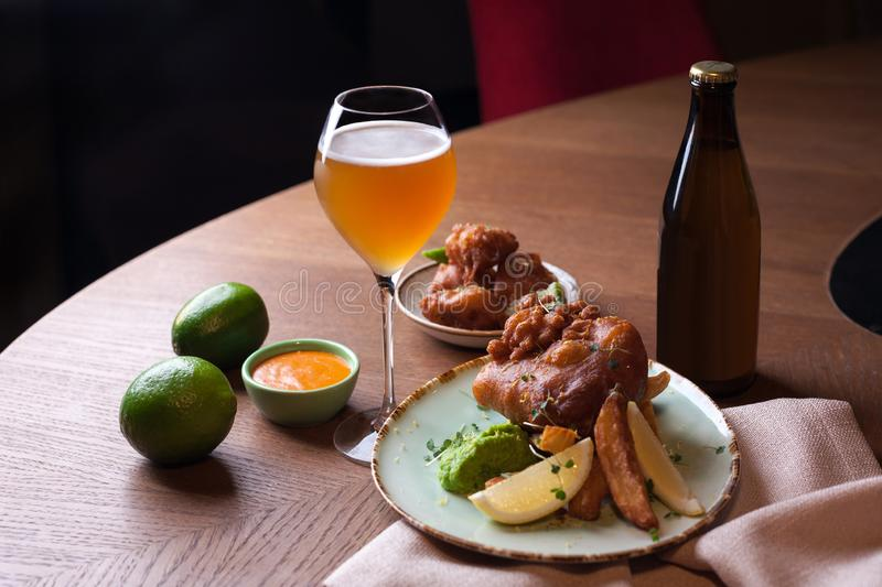 Battered fish with fried potatoes and glass of beer stock images