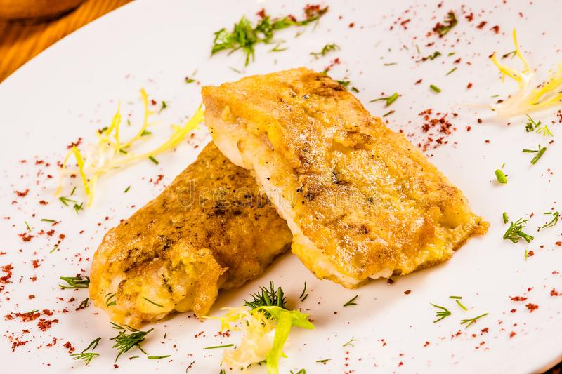 Battered fish with spices on white plate stock images