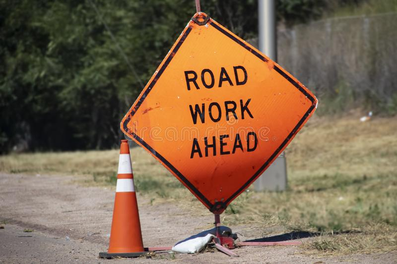 Battered Road Work Ahead sign and traffic cone sitting by road with blurred background.  stock photography